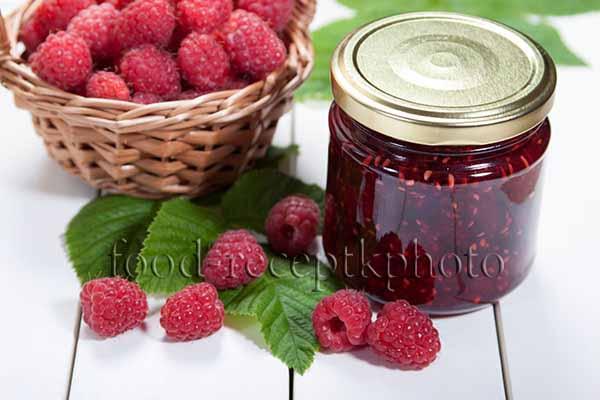 Малиновое варенье в стеклянной банке и ягоды малины в корзинке