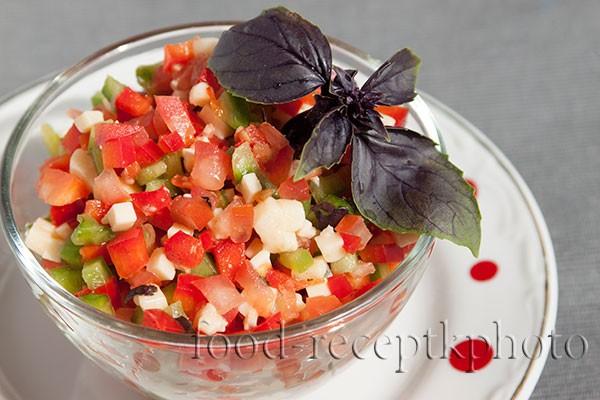На фото салат из помидор,болгарского перца с сыром и листьями базилика