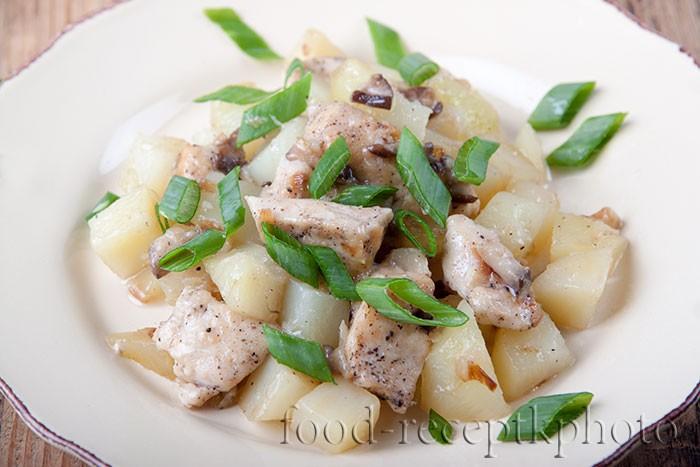 На фото жареный картофель с курицей, грибами и зеленым луком в тарелке