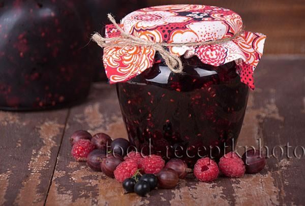 На фото банка с вареньем и ягоды малины,крыжовника и черной смородины на старом деревянном столе