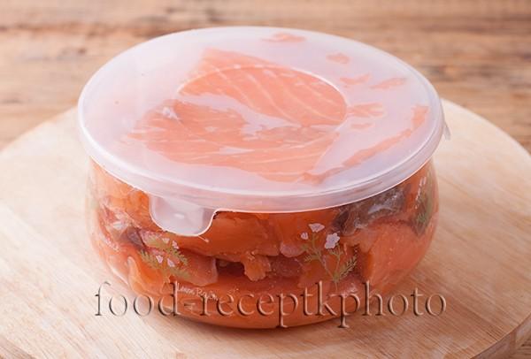На фото семга после засолки в стеклянном контейнере