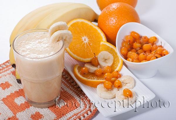 На фото смузи с облепихой,бананом и апельсином с стакане. Фрукты и ягоды рядом на столе.