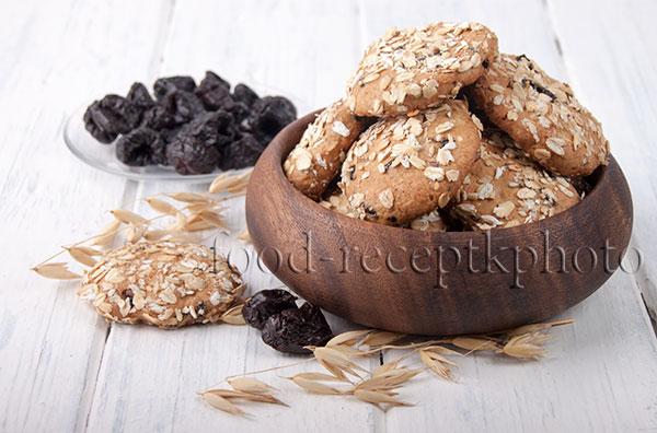 На фото овсяное печенье с черносливомв деревянной миске на белом столе. Рядом лежит печенюшка, колосья овса и чернослив