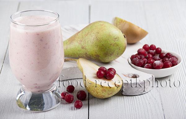 На фото  в стакане смузи из груши и клюквы и груши и ягоды клюквы на белой разделочной доске на белом деревянном столе