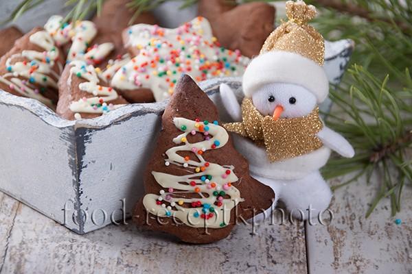 На фото сметанное печенье декорированное белым шоколадом и кондитерской посыпкой в деревянном ящичке и рядом игрушка снеговика и ветки ели