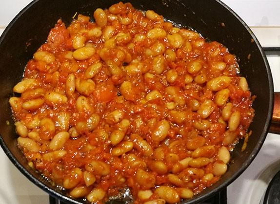 На фото в сковороде обжаривается репчатый лук,морковь,помидор ,чеснок и фасоль с томатной пастой