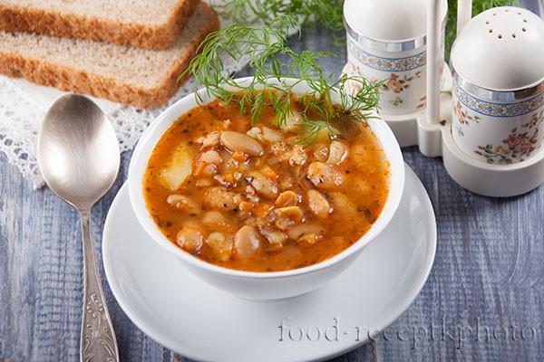 На фото фасолевый суп в белой тарелке с хлебом и сбаночками со специями на синем деревянном столе