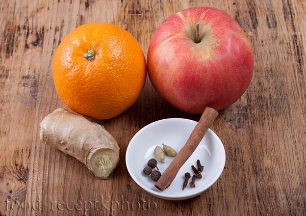 На фото на старом деревянном столе ингредиенты для фруктового пряного чая апельсин,яблоко,корень имбиря и специи