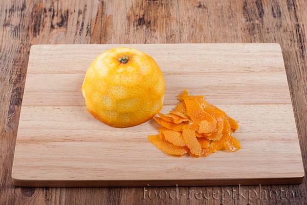 На фото на разделочной доске половина очищенного апельсина и цедра