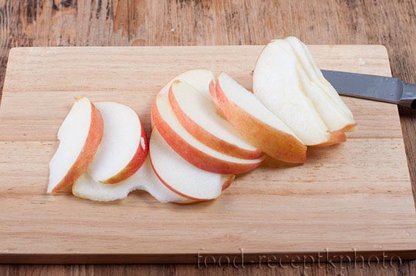 На фото на разделочной доске порезанное на дольки яблоко