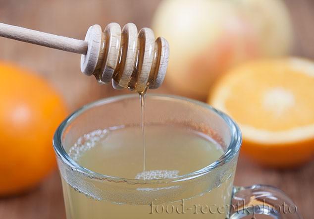 На фото пряный фруктовый чай в чашке для глинтвейна с ложечкой для меда с которой стекает мед