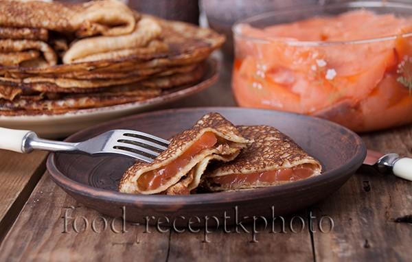 На фото стопка блинов в тарелке  и семга на старом деревянном столе