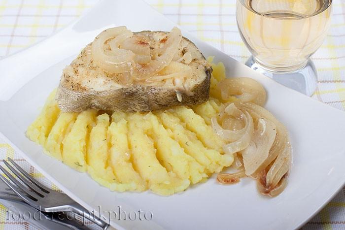 На фото треска с пюре репчатым луком в белой тарелке и рядом бокал вина
