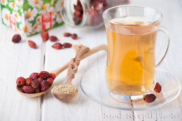На фото в стеклянной чашке чай из шиповника и ромашки, рядом с чашкой две деревянные ложки, в которых сухой шиповник и сухая ромашка, а на заднем плане видна коробка с цветами ромашки и банка с ягодами шиповника