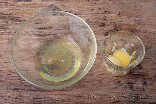 На фото стеклянный салатник с белками от яиц и стакан с желтками