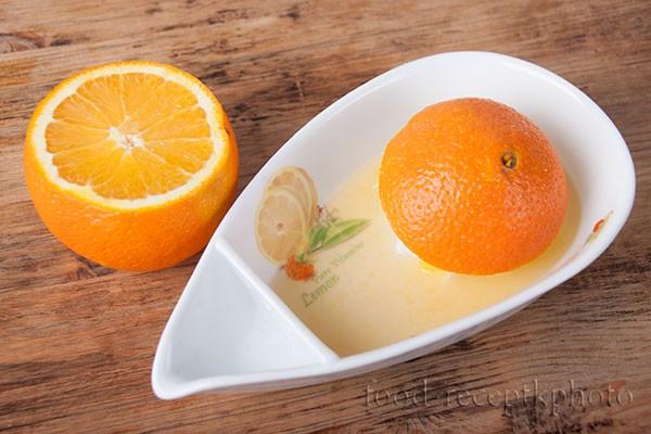 На фото разрезанный апельсин и соковыжималка для цитрусовых