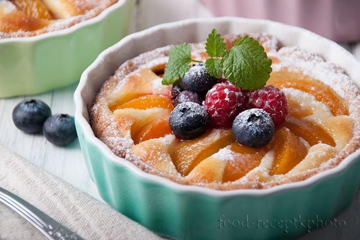 На фото в керамической формочке для запекания песочный тарт с творожной начинкой,персиками и ягодами