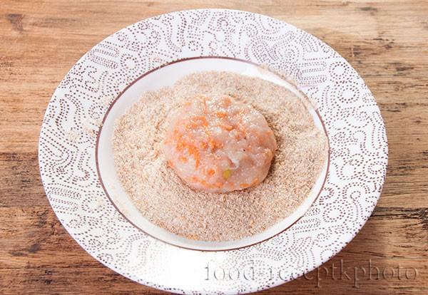 На фото в тарелке сформированная котлета в панировочных сухарях