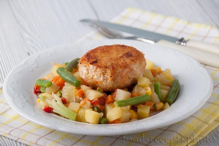 на фото в белой тарелке овощной гарнир с куриной котлетой