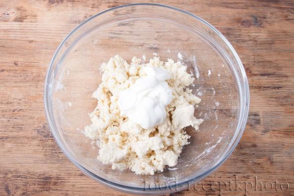На фото ингредиенты для приготовления теста для лукового пирога в стеклянном салатнике