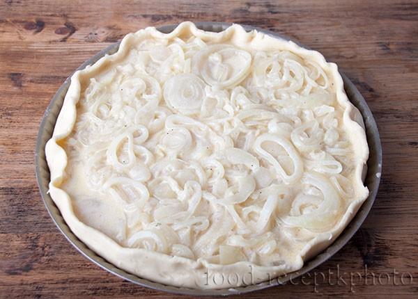 На фото луковый пирог в форме для выпечки до выпекания