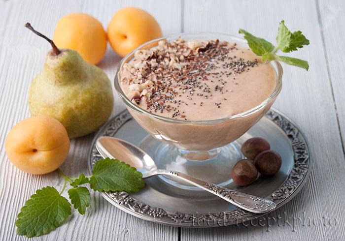 На фото в стеклянной креманке смузи из абрикосов и груши и рядом лежат фрукты абрикосы и груша