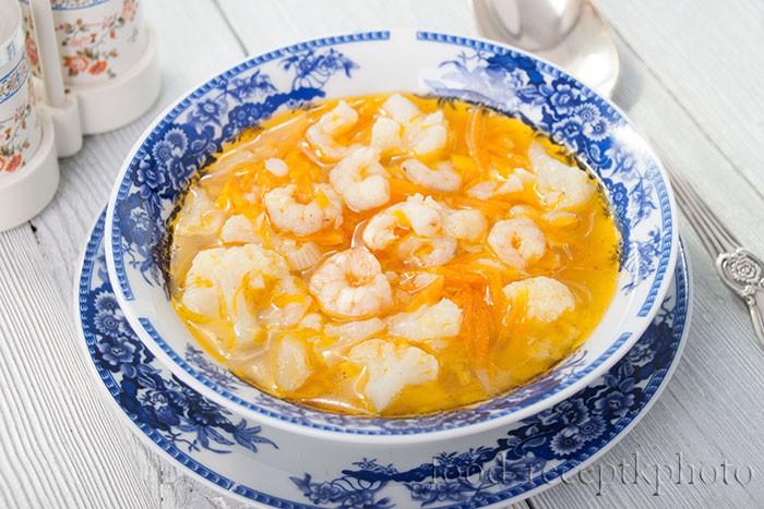 На фото синяя тарелка с узором с супом из цветной капусты с креветками