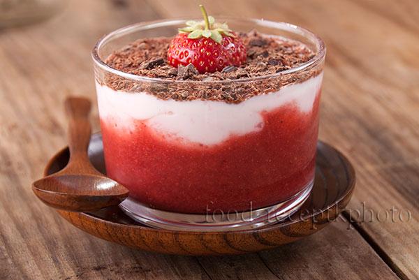На фото в стеклянном стакане клубничный десерт с протертой клубникой,йогуртом и шоколадом
