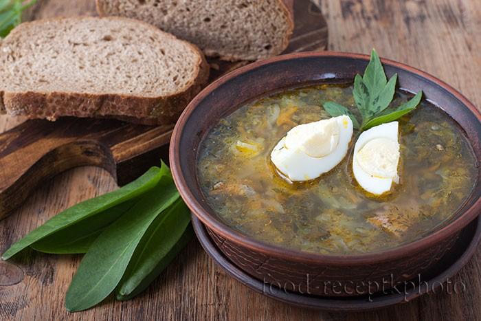 На фото в керамической тарелке щи из капусты с щавелем,нарезанный хлеб и щавель на деревянном столе