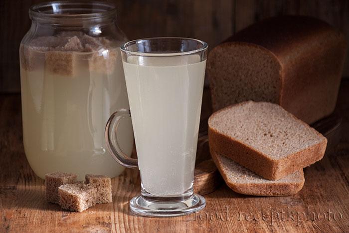 На фото в кружке хлебный квас и на заднем плане хлеб и банка с квасом