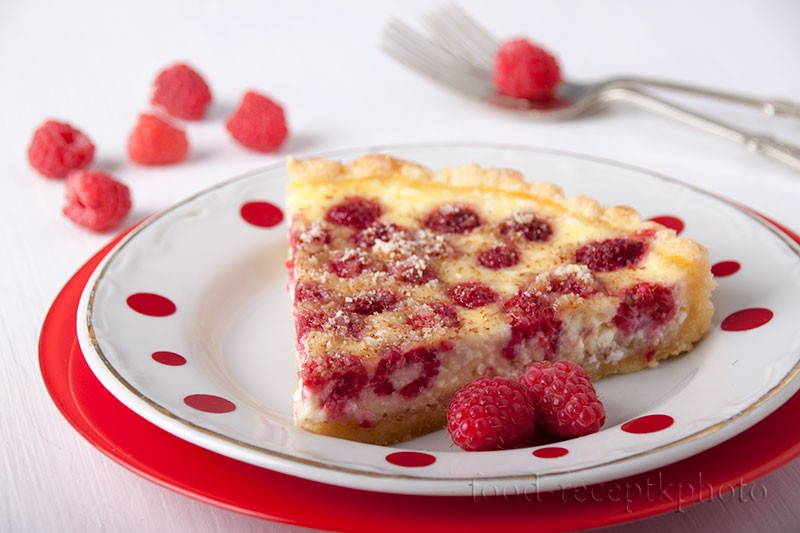На фото в тарелке кусок пирога с ягодами малины в сметанно-творожной заливке