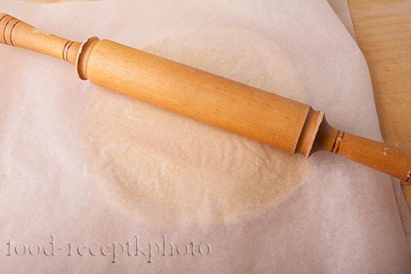 На фото песочное тесто на пекарской бумаге раскатываемое скалкой