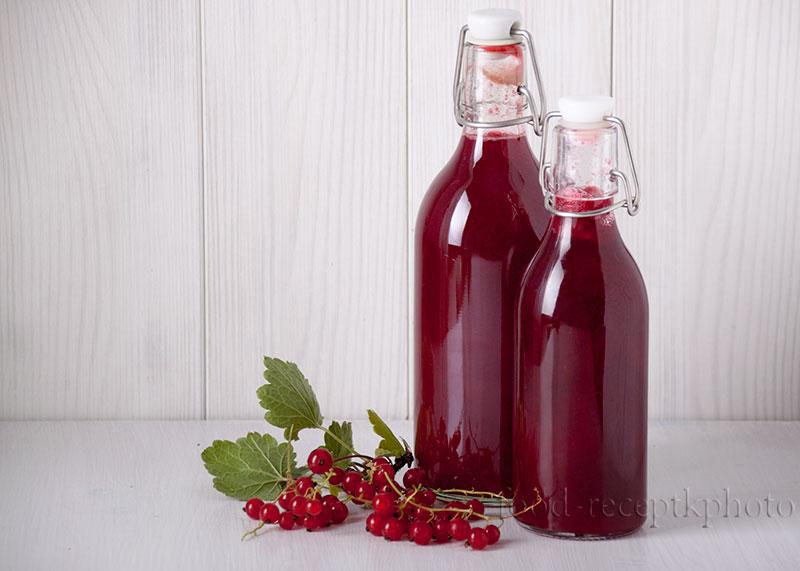 На фото две бутылки с соком красной смородины на белом деревянном столе на фоне белой деревянной стены