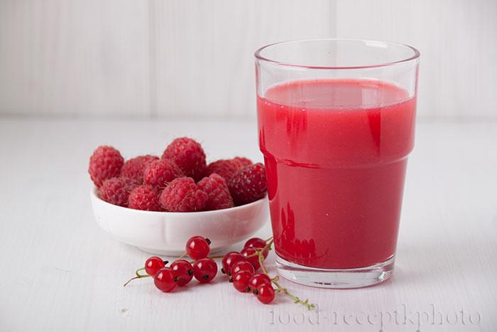 На фото стакан с киселем из малины и красной смородины
