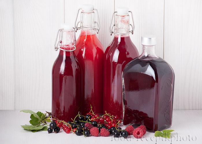 На фото бутылки с соком из ягод заготовки на зиму