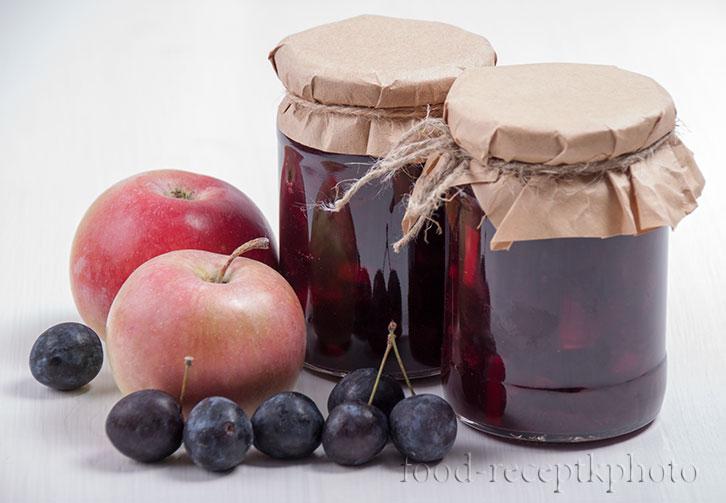 На фото две стеклянные банки с вареньем из тёрна с яблоками и рядом с банками тёрн и яблоки на белом столе