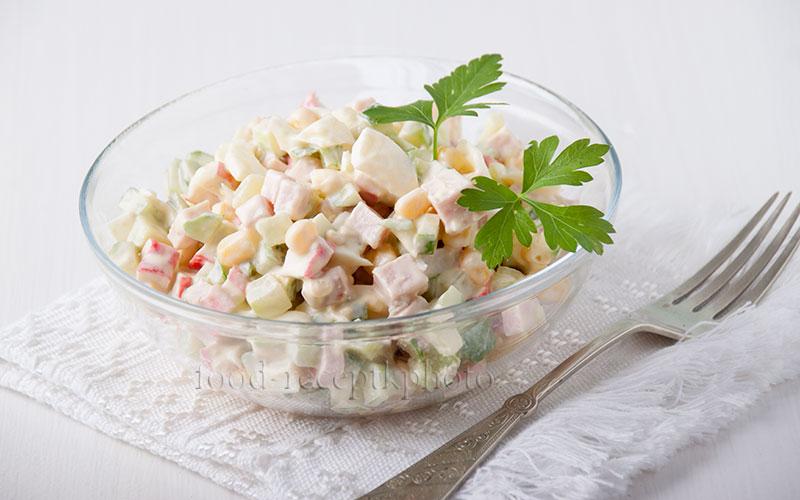На фото в стеклянном салатнике салат из крабовых палочек с мясом,яйцами,кукурузой и свежими огурцами