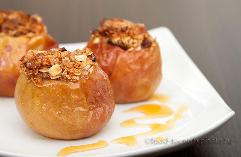 На фото яблоки с начинкой из мюсли в белой тарелке