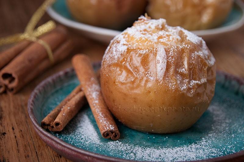 На фото печеное яблоко с сахарной пудрой в бирюзовой тарелке и палочки корицы