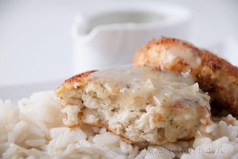 На фото в белой тарелке рыбные котлеты с гарниром из риса под соусом