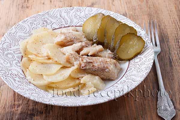 Щука запеченная с картофелем на тарелке с солеными огурцами