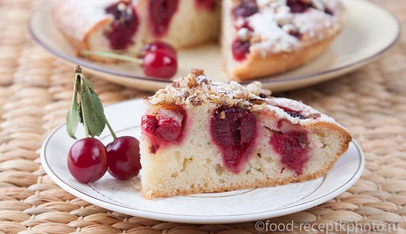 Вишневый пирог с грецкими орехами и ягоды вишни на белой тарелке
