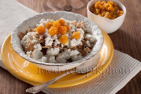 Творог с мюсли и моченой морошкой в белой тарелке