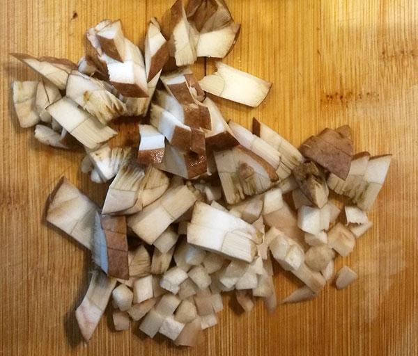 На фото мелко нарезанный свежий гриб подберезовик на разделочной доске