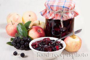 На фото варенье из аронии черноплодной с яблоками в стеклянной банке и вазочке для варенья, а также яблоки и ягоды аронии рядом на столе