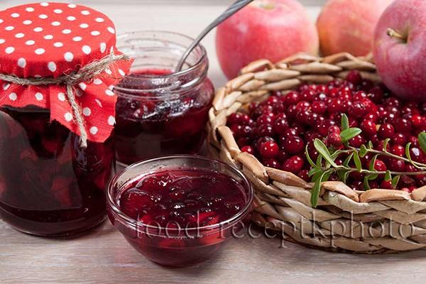 На фото варенье из брусники с яблоками в стеклянной банке и вазочке для варенья, и также ягоды брусники в плетеной корзинке и яблоки на заднем плане