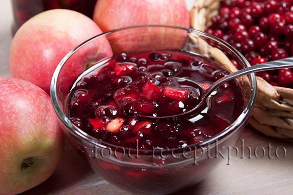 На фото варенье из брусники с яблоками в вазочке для варенья, яблоки и ягоды брусники в плетеной корзинке