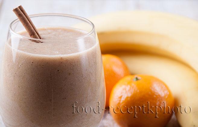 На фото смузи из мандаринов,банана с йогуртом в стакане и рядом орехи миндаля, палочки корицы и фрукты мандарины и бананы