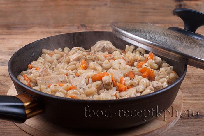 На фото макароны с куриным мясом и овощами в сковороде