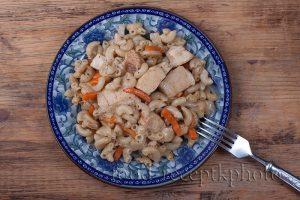 На фото макароны с куриным мясом и овощами в синей тарелке на деревянном столе